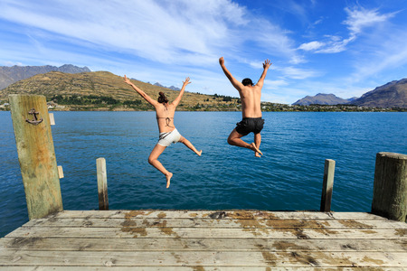 Young couple jumping on the edge of a dock into the Lake Wakatipu Stok Fotoğraf - 41859202