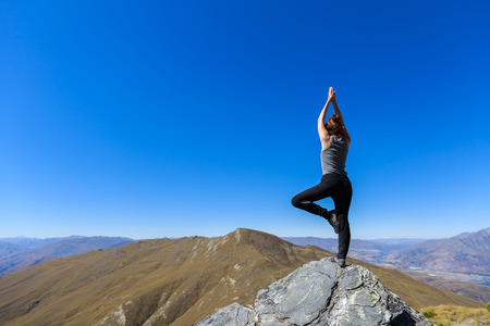 Young woman practicing yoga on top of the mountain, Ben Lomond, New Zealand