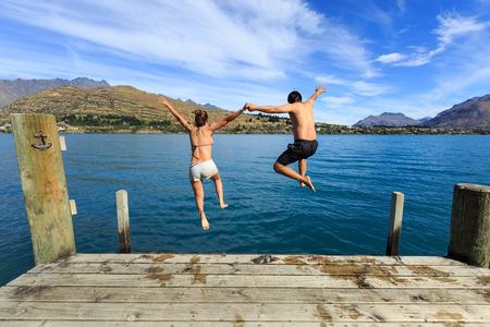 wakatipu: Young couple jumping on the edge of a dock into the Lake Wakatipu Stock Photo