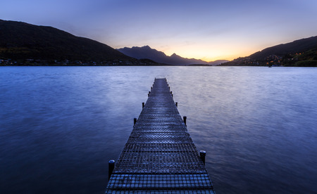 long lake: wooden pier on big lake in Queenstown, New Zealand Stock Photo