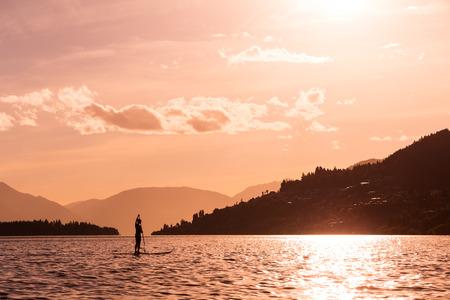 wakatipu: young female paddles a paddleboard off Lake Wakatipu at the sunset