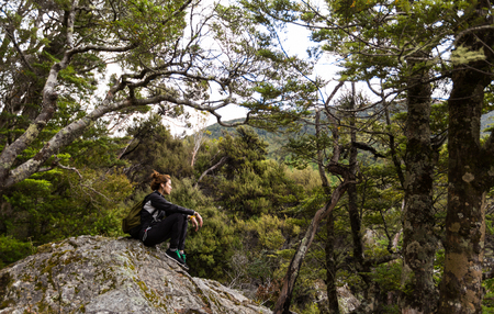 sylvan: young adult woman take a rest on the rock at Lake Sylvan Track, New Zealand
