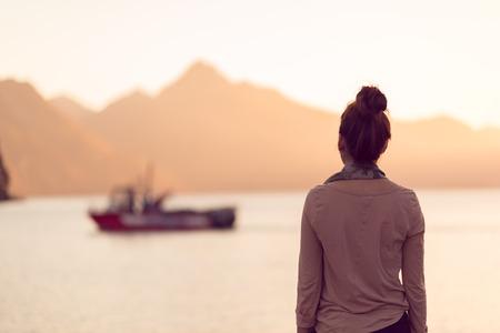 Joven mujer adulta que mira en el lago al atardecer Foto de archivo - 42097617