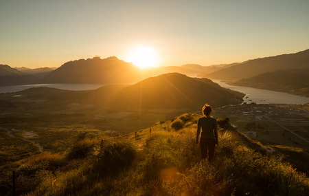 Woman silhouette at sunset on the mountain. New Zealand