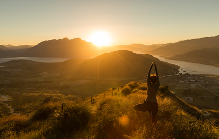 mountain scene: Woman practicing yoda silhouette at sunset on the mountain. New Zealand