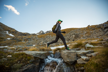 new horizons: Female hiker with backpack leaping across a stream. New Zealand