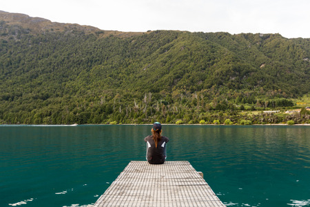 woman sitting on pier