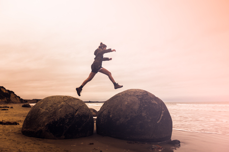 Long exposure image of young adult woman jumping on Moeraki Boulders, South Island New Zealand
