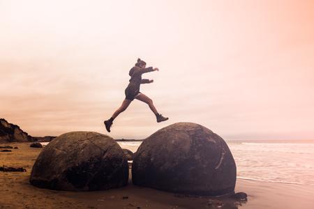 Moeraki 巨石、ニュージーランド南島にジャンプの若い成人女性の長時間露光画像