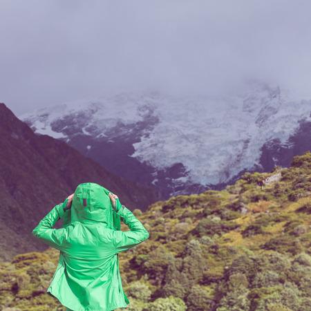 put on: female hiker put on jacket.