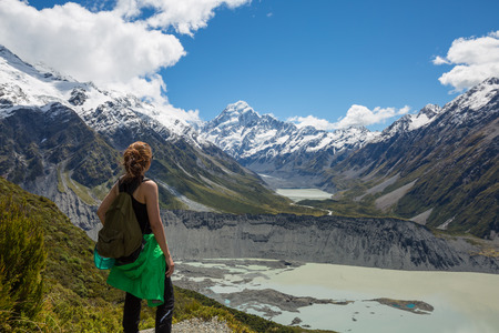 Woman Traveler with Backpack hiking in Mueller Hut Route, Mount Cook National Park, New Zealand
