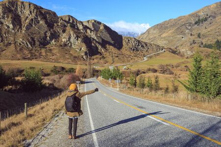 hitch: woman with backpack hitch hiking. New Zealand