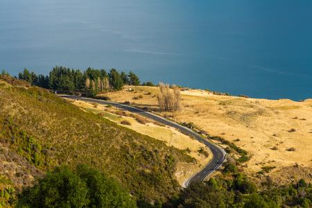 guardrail: aerial view of road along Lake Wakatipu, New Zealand Stock Photo