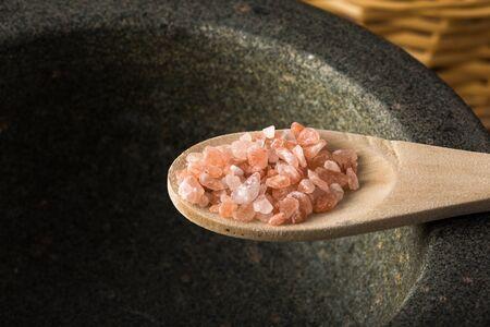 rock salt: Spoonful of pink Himalayan rock salt, over granite mortar
