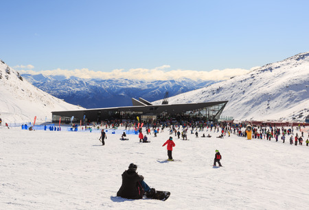 Ski Area: QUEENSTOWN, NEW ZEALAND - AUGUST 6: Tourists enjoy skiing and snowboarding in front of new base building at the Remarkables Ski Area on August 6 2015 in Queenstown, South Island, New Zealand
