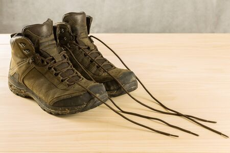 hiking shoes: pair of dirty men hiking shoes on wood table