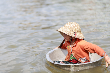 tonle sap: TONLE SAP LAKE SIEM REAP, CAMBODIA - JANUARY 10: unidentified girl use basil as a boat to travel around the village on January 10, 2012 at Tonle Sap Lake, Siem Reap Cambodia