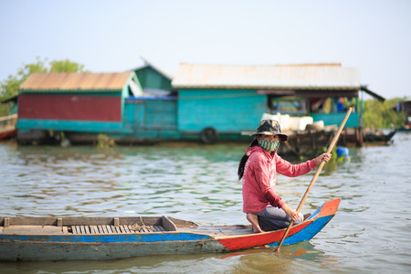 lake front: TONLE SAP LAKE SIEM REAP, CAMBODIA - JANUARY 10: unidentified girl paddle from front part of a boat on January 10, 2012 at Tonle Sap Lake, Siem Reap Cambodia Editorial
