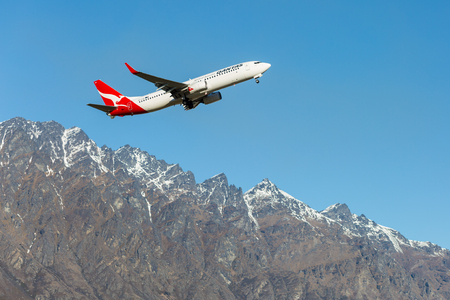 voted: Queenstown, New Zealand - September 1: Qantas plane takes off in Queenstown International Airport on September 1, 2014 in Queenstown, New Zealand. Queenstown International Airport  has been voted the worlds most scenic airport approach