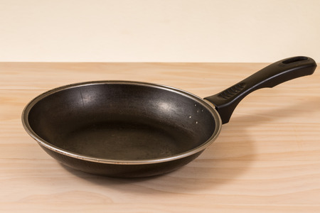 non: used non stick frying pan on wooden table Stock Photo