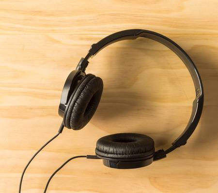 audifonos: auriculares negros sobre fondo de madera