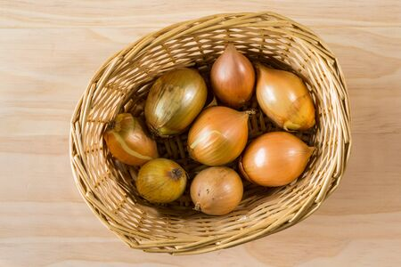 overhead shot: overhead shot image of onions in basket on wooden background Stock Photo