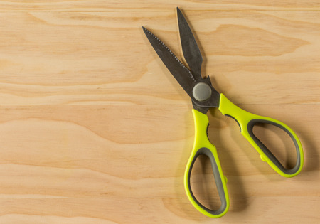 overhead shot: overhead shot image of green kitchen scissors on wooden background