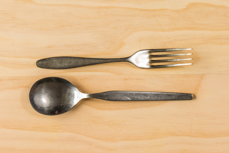 overhead shot: overhead shot image of fork and spoon on wooden table