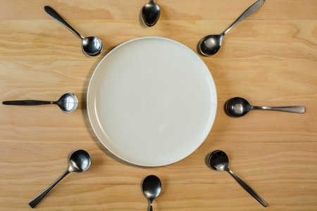 overhead shot: overhead shot image of white plate surrounded with spoons