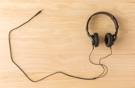 electronic music: black headphone on wooden background Stock Photo