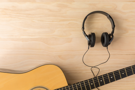 musical instruments: Acoustic guitar and headphone on wooden background