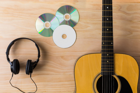 musical instruments: Acoustic guitar, cd and headphone on wooden background Stock Photo