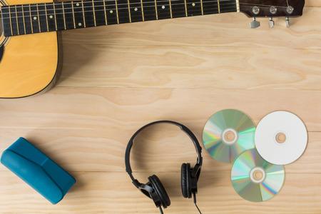 instrumentos de musica: Guitarra acústica, cd y auriculares sobre fondo de madera
