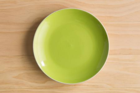 木製の背景に緑のプレート