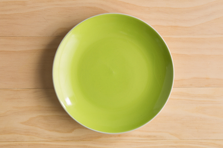 plates: green plate on wooden background