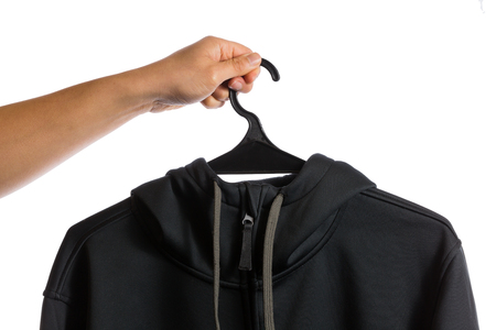 hoody: hand holding cloth hanger with black hoody isolated on white background