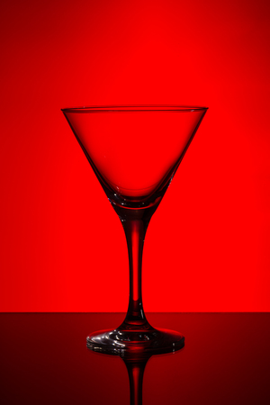 cocktail glasses: empty martini glass on red background