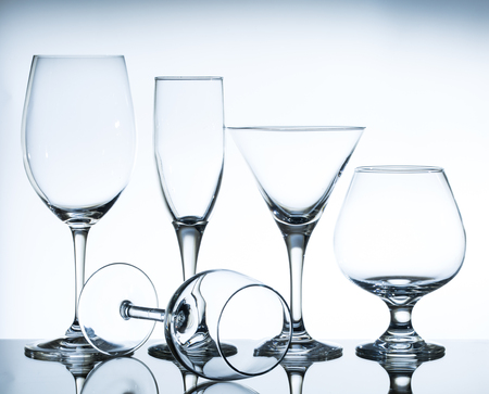 cocktail glasses: empty wine glasses on the glass table and white background