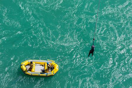 Queenstown, Nueva Zelanda - 11 de octubre: El equipo de Bungy AJ en bote de goma utilizar palo largo para captar su cliente después de salto bungy del puente de Kawarau el 11 de octubre, 2015, en Queenstown, Nueva Zelanda Foto de archivo - 46258101