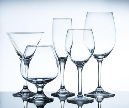 anteojos: copas de vino vacías en la mesa de cristal y un fondo blanco Foto de archivo
