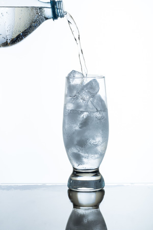 soda water: pouring soda water into a glass of ice