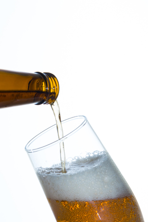 pouring beer: pouring beer into a glass on white background Stock Photo