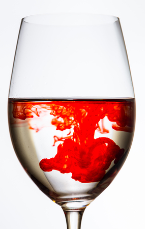 clean blood: drop of red color spreading in wine glass on white background