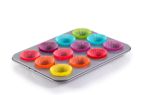 muffins baking tray with colourful paper cases isolated on white