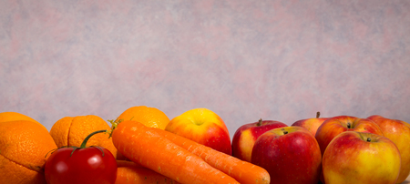 unwashed: mixed red and orange fruit and vegetable (oranges, tomato, carrots and apples) Stock Photo