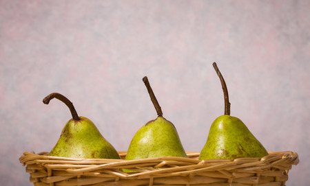 close up image: close up image of three pears in a basket