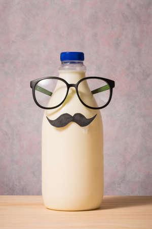 milk mustache: bottle of milk on wooden table