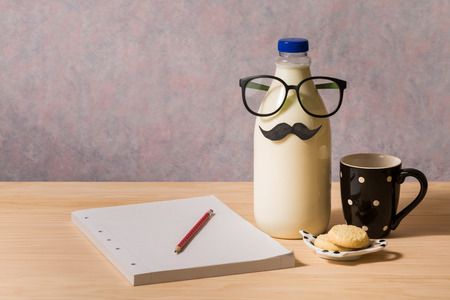 milk and cookies: bottle of milk, cookies and notebook on wooden table Stock Photo