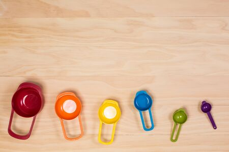 measuring spoons: colorful measuring spoons on wooden background Stock Photo