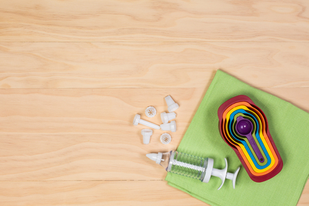 measuring spoons: colorful measuring spoons and Cake decoration icing syringe and set of nozzles on wooden background
